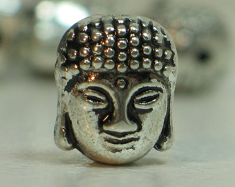 Small double-sided Buddha heads in Tibetan silver