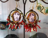 "earrings with faces of Fornasetti painting ""What kind of women are you"" made with gass pearl coral and golded silver"