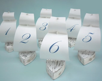 6 white sailboats with blue numbers