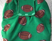 Reversible Baby Car Seat Cover is green with a football print on one side and solid gold on other side. - CreationsForKids