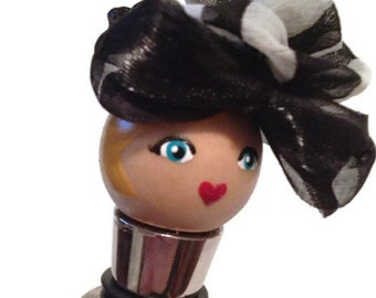 Wine stopper: blonde doll wearing a black and white hat