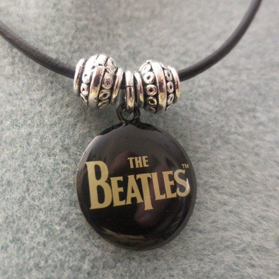 Beatles logo with silver beads on black leather.  Man's necklace