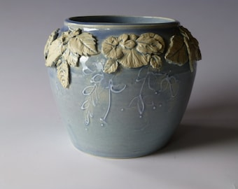 blue vase with white leaves and flowers