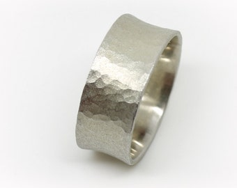 Gentle hammered silver wedding band with a matte finish .