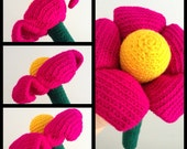 Annie - Giant Crochet Flower with a warm yellow centre surrounded by fuchsia petals and accentuated by dark green stem