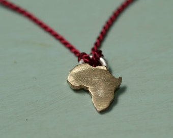 Tiny brass africa continent pendant on a silk cord