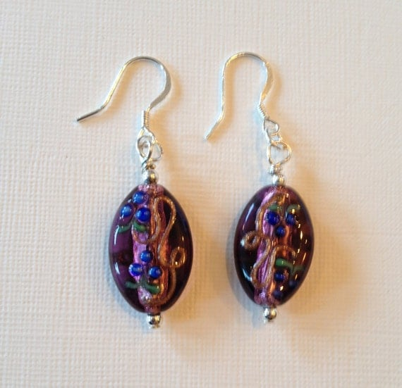 Earrings with purple glass beads that include pink, blue, green and golden touches