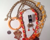 3 orange necklaces and 1 pair of earrings