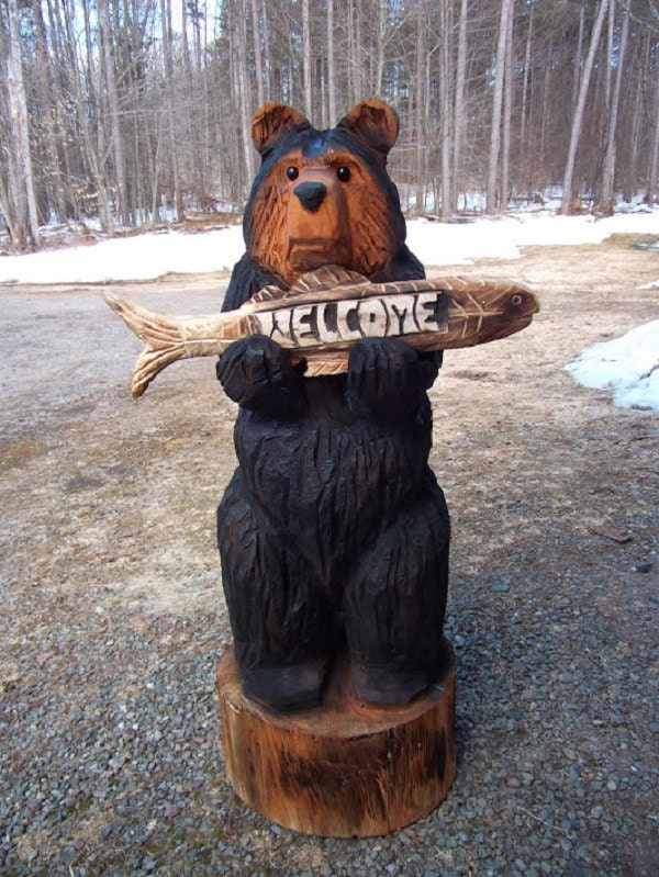 Carved black bear holding fish welcome sign