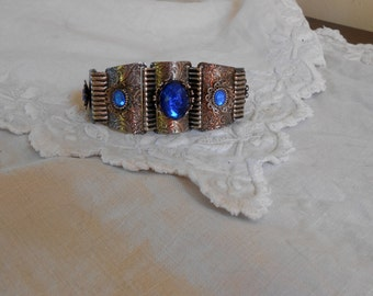 1940s deco stamped silver bracelet with blue Vauxhall glass ... baroque floral swirls, showy design ... Mexican flavor