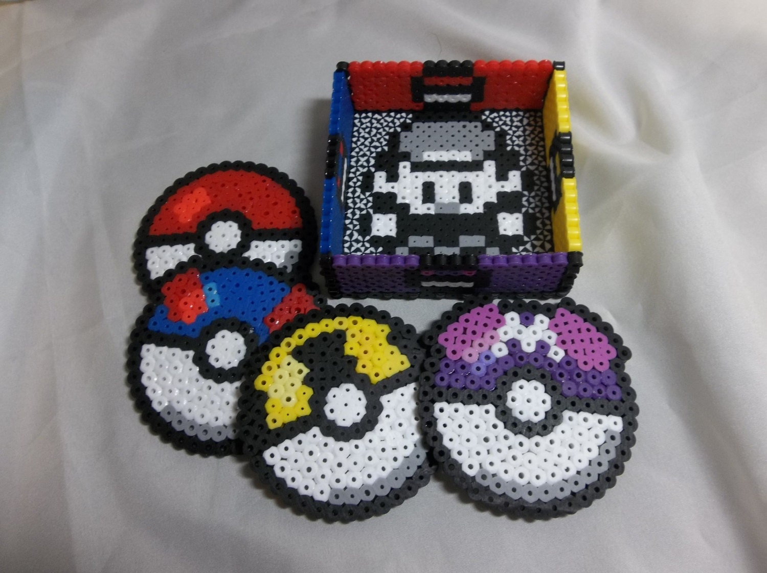 set of four pokeballs with pokemon trainer container