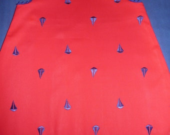 Red jumper embroidered with blue sail boats.