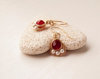 Red crystal gold earrings with pearls around them