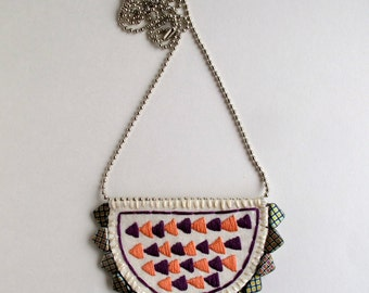 Hand embroidered pendant necklace with triangle arrows in peach and plum colors on crescent shape with Czech glass beads An Astrid Endeavor