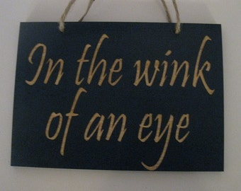 In the wink of an eye wooden sign