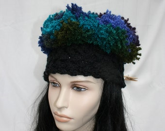 Handknitted cabled hat with frilly yarns