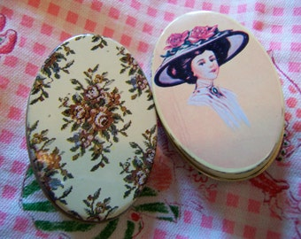 two tiny oval tin boxes