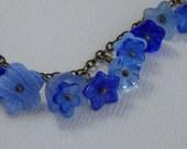 Pretty charm bracelet full of blue flowers 7.375 inches B202B
