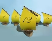 rustic sailboat table number holder with yellow sails