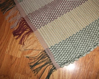 Hand-woven rag rug made of recycled light green fabric with a multi-colored warp