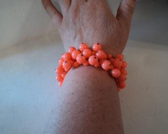 A vintage florecent orange beaded elastic bracelet on elastic cord