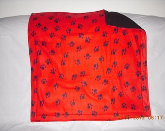 Pet Blanket - black paws on red print fleece with solid black fleece on reverse side.