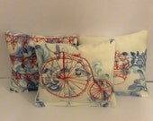 Machine embroidered lavender bags with penny farthing, bunting and a crown in red white and blue.