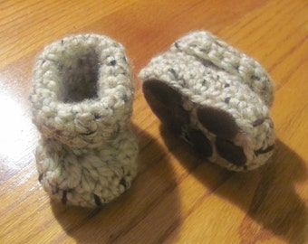 Newborn crochet baby booties with paw prints.