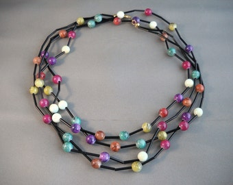 Multiple colors, black accented, very long double strand necklace.