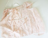 A Soft Tricot Nylon Pink Baby Bib With White Ribbon Drawstring Around the Neck and Two Deep Pockets - From the 1940s - Light and Airy
