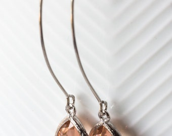 Sparkling Pastel Peach Teardrop Glass Earrings With A Shiny Silver Tone Frame