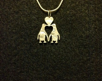 Two penguins and heart coin jewelry pendant cut from a golden dollar