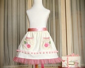 Girls or toddlers cream corduroy skirt with pink tulle trim and decorated pockets.