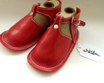 Red leather baby shoe with buckle and rivet