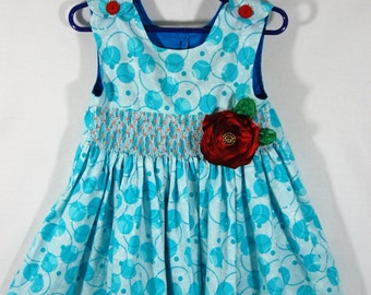 Smocking dress in turquoise with circles pattern fabric embelished with satin flower