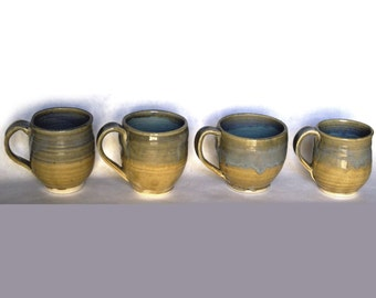 Set of four tan and green mugs