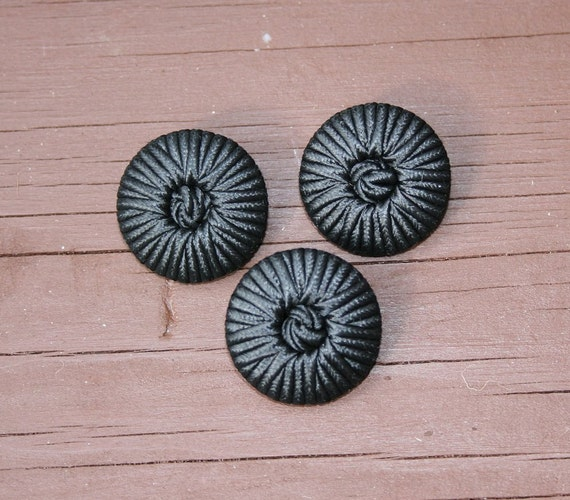Three black braid covered buttons with a knot in the centre and a plastic shank at the back in 23mm size