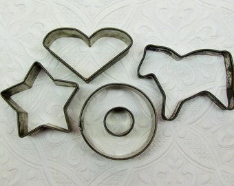 Antique cookie cutters, lot of 4 early tin cookie and doughnut cutters, horse, star, heart, and 2 piece doughnut cutter