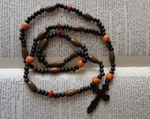 Wooden rosary with oval and orange painted beads and Russian style wooden cross