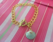 COACH Scallop Shell Charm on Gold Plated Charm Bracelet.