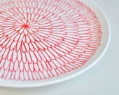 Hand Decorated White curved plate in geometric abstract petal pattern in red