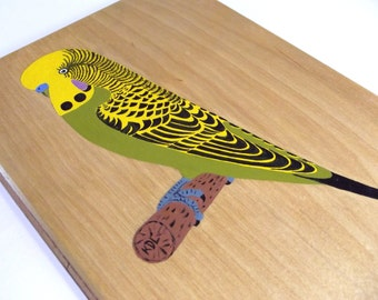 Vintage painting on wooden board of a yellow/green budgerigar sitting on a branch