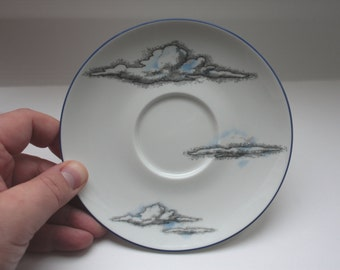 Upcycled stoneware porcelain plate with cloud illustrations.