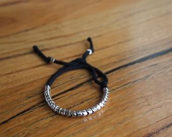 Sterling Silver Bracelet snake like beads on black cotton thread.