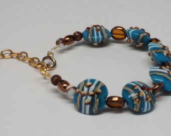 Bracelet with Handmade Lampwork Glass Sky Blue Lentil Beads Amber Toned Beads Gold Toned Findings Spring Clasp