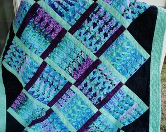 Handquilted lap quilt done in stacked cutting design in blues and purples