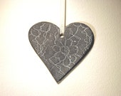 Large ceramic heart ornament with lace pattern. Dark brown and white.