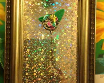 Miniature floral sculpture,painted button and green leaves hand made clay,framed with holograph paper