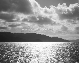 Photography black and white: dramatic clouds over sea with bright sun sparkling, island silhouette, bold striking art, ready-to-frame print