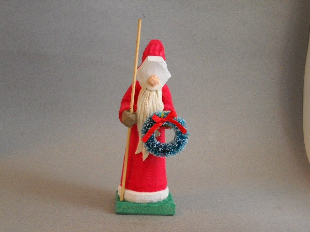 Red robed Santa holding his staff and a wreath.